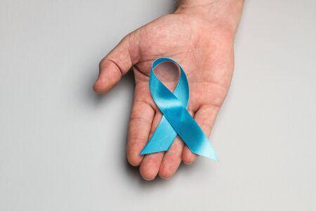 A blue ribbon on a man hand