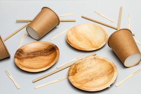 Paper cups, plates and sticks on a gray background