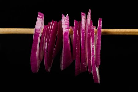Slices of a purple onion hanging from a wooden stick Фото со стока