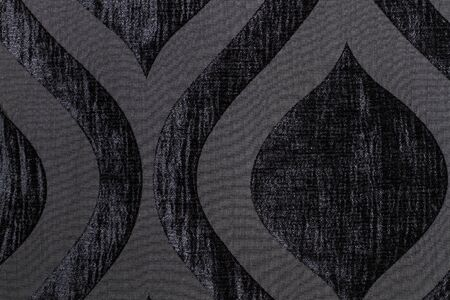 A texture of a black wool textile with ornaments