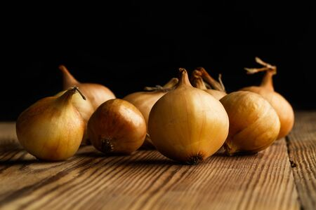 Small white french onions on a wooden table on a dark background