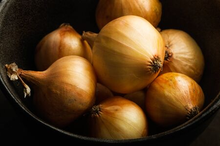 Small white french onions in a dark bowl