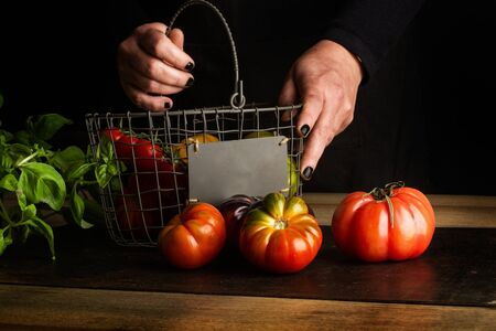 Woman putting differents tomatoes in a wire basket