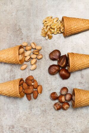 Ice cream cones with nuts on a marble table