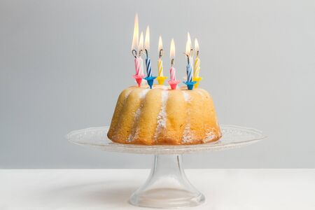 A birthday bundt cake with colored burning candles