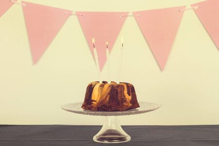 A chocolate and vanilla bundt cake with burning candles