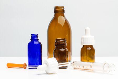 Medical bottles with droppers on a white table