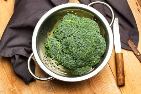Broccoli in a strainer on a wooden table