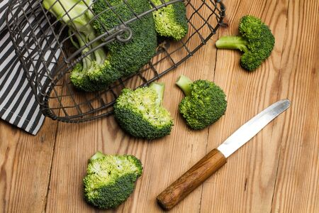 Broccoli in a basketball on a wooden table