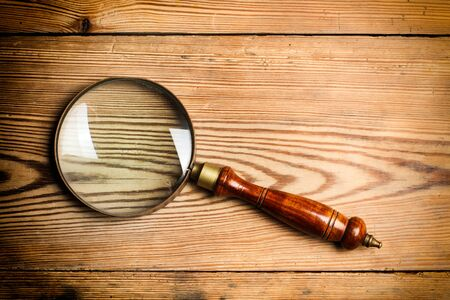 A magnifying glass on a wooden table in a close up view Zdjęcie Seryjne