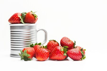Red delicious strawberries in a mug and on a white background Zdjęcie Seryjne