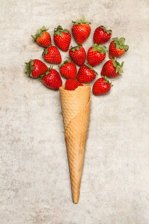 Delicious strawberrys and an ice cream cone on a marble table