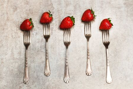 Strawberrys and forks on a marble table