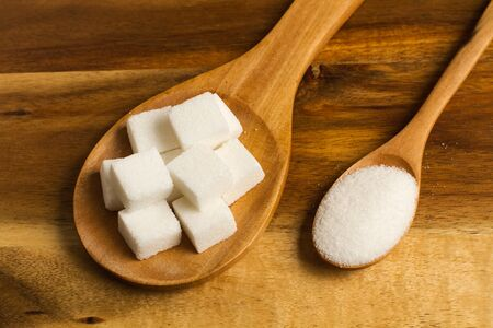 Brown sugar cubes on a wooden spoon and a wooden spoon with brown sugar