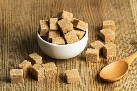 Brown sugar cubes in a white bowl and on a wooden table
