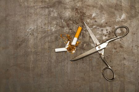 A broken cigarette and scissors on a rusty metal background Stock Photo