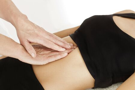 Professional massages to a woman on her abdomen on a stretcher