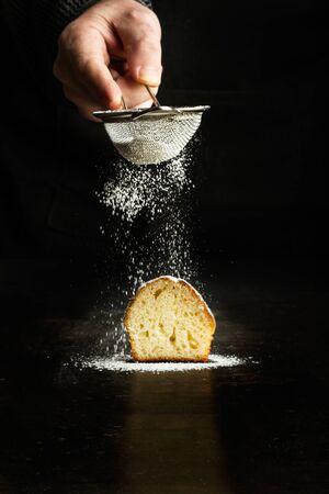 Man sprinkling powdered sugar on a cupcake on a dark background