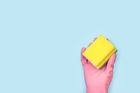 A hand with a pink rubber glove holding a cleaning sponge on a light blue background