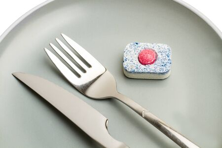 A dishwasher tablet on a gray plate with a fork and a knife Stock fotó