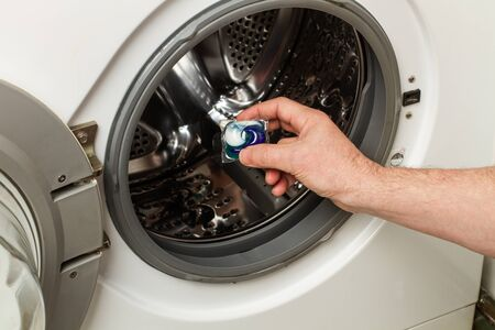 Man holding a laundry pod in front of a washing machine door