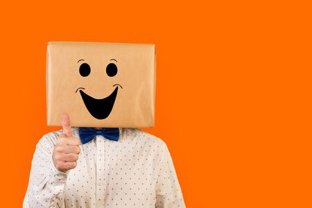 Man standing with his head in a box and laughing gesture drawn on it, with thumb up on a orange background