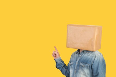 Man with a box on his head and pointing fingers on a yellow background Banco de Imagens