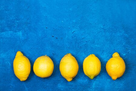 Five lemons on a textured classic blue background in a top view