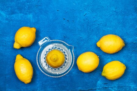 Lemons and a citrus squeezer on a textured classic blue background in a top view 版權商用圖片