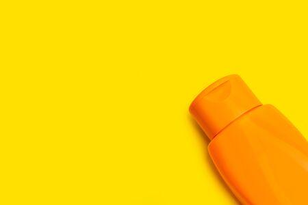 An orange suntan cream bottle on an orange background