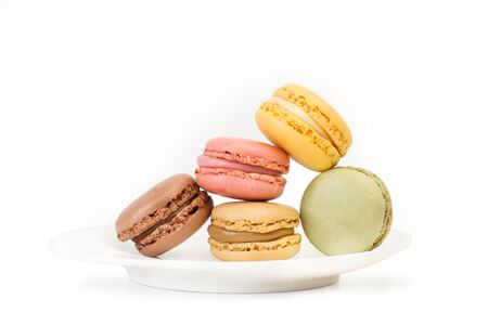 Multicolored macarons isolated on a white plate and on a white background