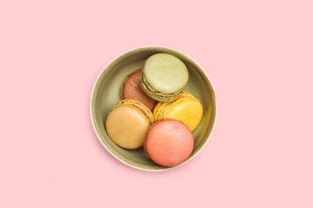 Colored macarons in a green bowl on a pink background in a top view Archivio Fotografico