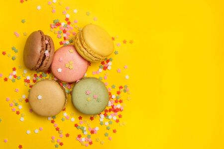 Colored macarons with star shape sprinkles on a yellow background in a top view Archivio Fotografico