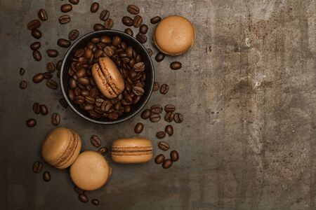 Coffee taste macarons with coffee beans on a dark metal table in a top view