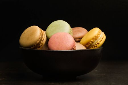 Colored macarons in a black bowl on a dark background