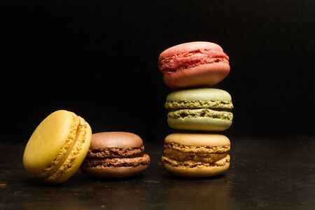 A heap of colored macarons on a metal table and on a dark background