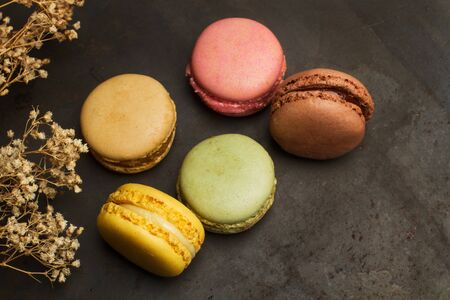 Colored macarons on a metal table in a top view