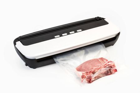 Vacuum packing machine and meat in a plastic bag on a white background