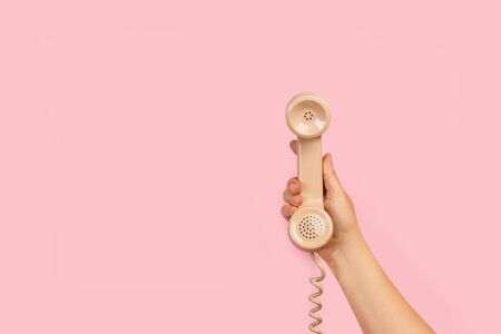 Woman´s hand holding an old phone on a pink background with copy space Banque d'images