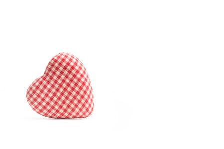 A heart made with red and white checked fabric isolated on a white background and with copy space