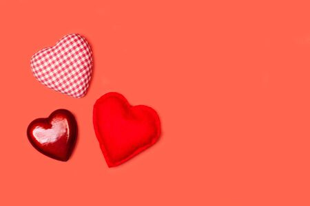 Three hearts made with fabric and plastic on a red background in a top view Imagens