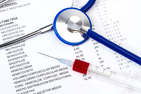 A stethoscope on a medical evaluation results and a syringe with blood Imagens