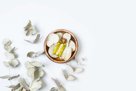 Branches with eucalyptus leaves and a bottle of essential oil in a top view with copy space