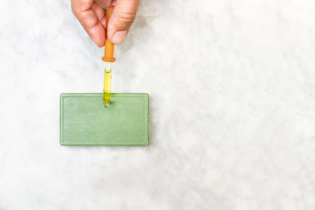Woman hand holding a dropper with skin oil on a green soap bar on a marble table in a top view