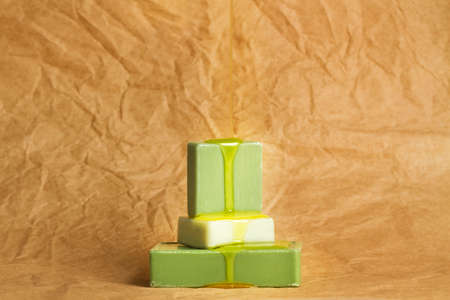 Dropping skin oil on green soap bars on a wrinkled brown paper