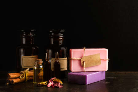Colored soap bars with old pharmacy bottles on a dark background