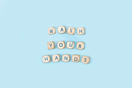 Wash your hands write with wooden letter cubes on a light blue background