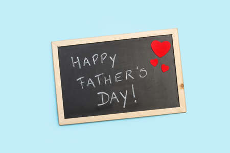 Blackboard with fathers day greeting on a light blue background