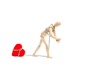 A wooden mannequin toy dragging a red textile heart with a chain on a white background