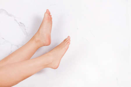 Woman legs and foot on a marble background with copy space